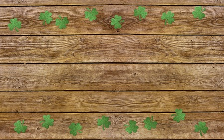 Paper clover leaves on the old wooden background. Lucky shamrock, St.Patricks day holiday symbol. Space for text, top view