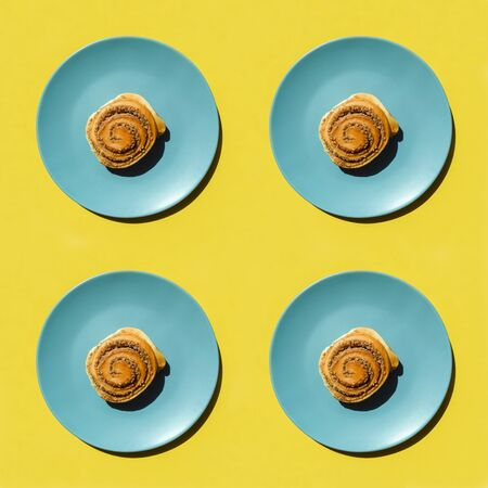 Sweet buns in blue plate isolated on yellow. Top view. Sweet cinnamon rolls pattern. hard shadow