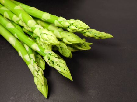 Bunch of raw asparagus. Fresh green asparagus on a black background. 写真素材