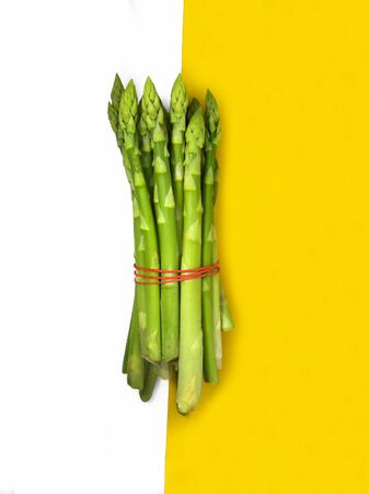 Raw asparagus. Fresh green asparagus on a yellow background.
