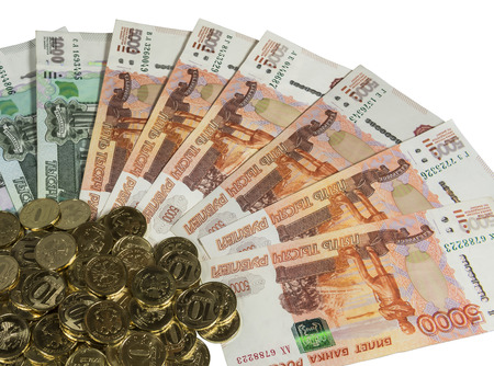 accrual: Denominations of 1000 and 5000 rubles spread out like a fan on a white background. In the corner of a scattering of coins of 10 rubles.