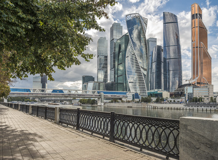 Green trees along the pedestrian sidewalk on the Waterfront of Taras Shevchenko on the background of Moscow city.