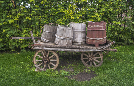 Old wagon full of old wooden barrels.