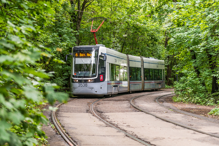 Moscow, Russia - July 8, 2016: City tram goes among the green thickets of trees.