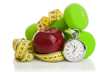 Zwei Hanteln, roten Apfel, Maßband und eine Stoppuhr isoliert auf weißem Hintergrund. Diät-Konzept.
