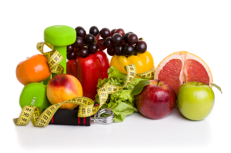 to the diet: fitness equipment and healthy food isolated on white. green and red apples, pepper, grapes, grapefruit, parsley, nectarines, dumbbells and measuring tape