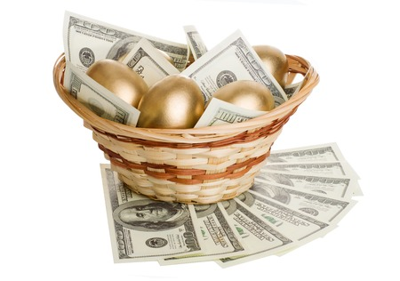 retiring: golden eggs and dollars in a basket isolated on white background Stock Photo