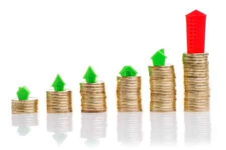 Stosy monet, zielonym i czerwonym domu z kompasem. Zdjęcie Seryjne