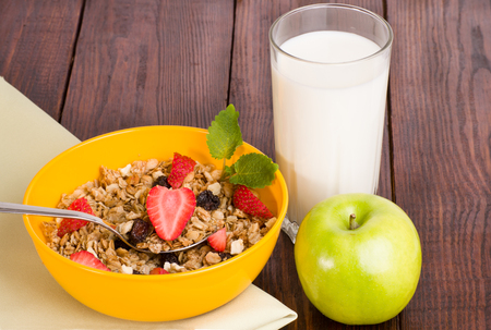 musli: muesli with strawberries, apple and a glass of milk on a green napkin Stock Photo