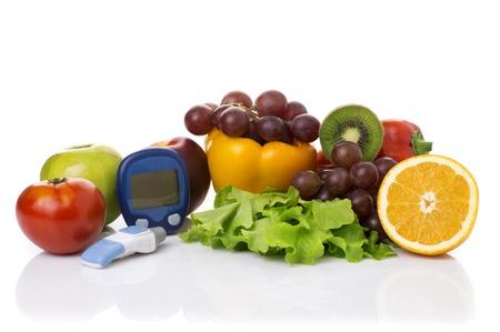 diabetes: glucómetro para el nivel de la glucosa y los alimentos orgánicos saludables sobre un fondo blanco. concepto de la diabetes