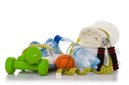 muscle toning: fitness equipment isolated on white. towel, two green dumbbells, shoes, ball, stopwatch and bottle of water.