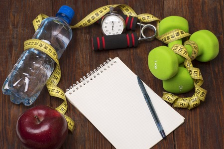 sports equipment: Workout and fitness dieting copy space diary. Healthy lifestyle concept. Apple, dumbbell, water, expander hand, stopwatch and measuring tape on rustic wooden table.