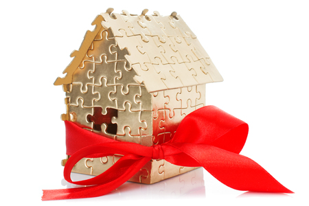 architectural model: Real estate concept - Hand holding house architectural model with red bow on it, isolated