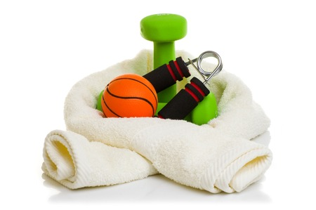 muscle toning: fitness equipment isolated on white. towel, two green dumbbells, simulator for hand, ball and bottle of water.