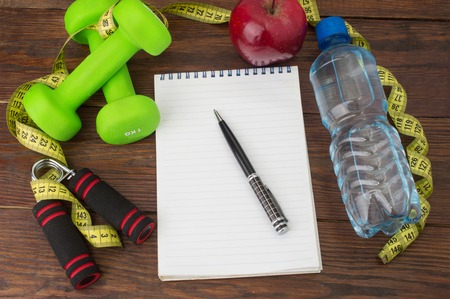 heavy weight: Workout and fitness dieting copy space diary. Healthy lifestyle concept. Apple, dumbbell, water, expander hand, stopwatch and measuring tape on rustic wooden table.