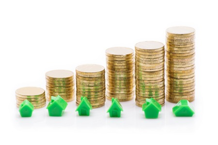 economic rent: Stacks of coins, green and red home with compass. Stock Photo