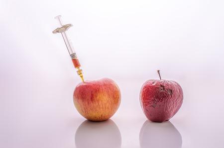 Ripe fresh apple fruit and wrinkled peel apple fruit getting rejuvenation injection procedure. Rejuvenation concept Aging concept. Reklamní fotografie