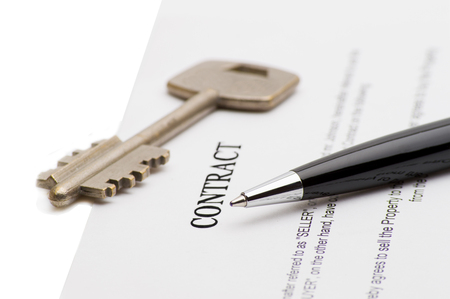handover: Keys of a new house on a signed contract of house sale with money in background. Concept of closed deal. Stock Photo
