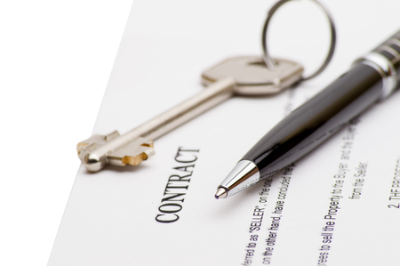 key handover: Keys of a new house on a signed contract of house sale with money in background. Concept of closed deal. Stock Photo