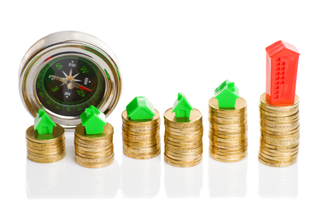 Stacks of coins, green and red home with compass. Mortgage concept by money house from coins Stock Photo