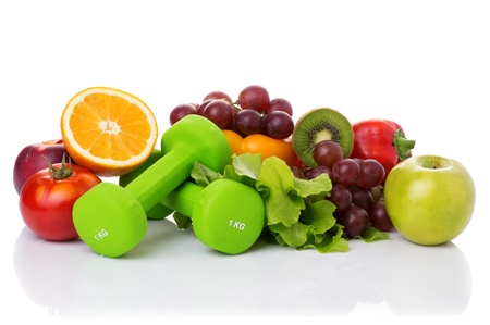 muscle fiber: fitness equipment and healthy food isolated on white. green apple, pepper, grapes, nectarines, kiwi, orange, dumbbells and measuring tape Stock Photo