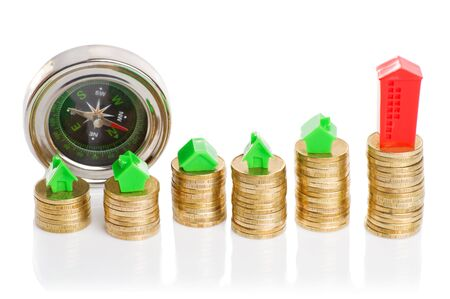 economic rent: Stacks of coins, green and red home with compass. Mortgage concept by money house from coins Stock Photo