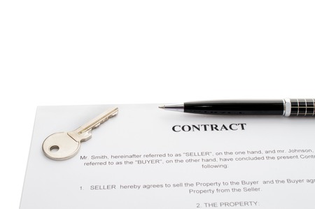 signed: Keys of a new house on a signed contract of house sale with money in background. Concept of closed deal. Stock Photo