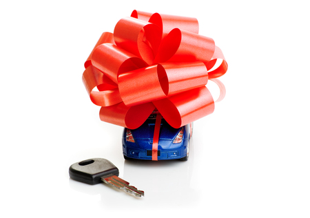 Car keys on the background of the machine with a red bow isolated on white background. Gift 스톡 콘텐츠
