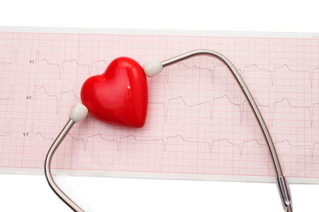 Cardiogram with stethoscope and red heart on table, closeup