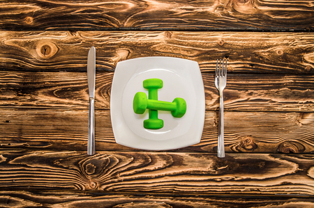 expander: Dumbbells, ball and expander on a plate as a breakfast, concept of healthy lifestyle, on a wooden table