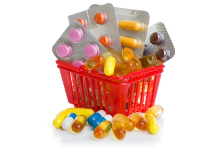 Colorful pills in shopping cart. Shopping trolley with pills and medicine isolated on white.
