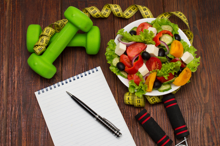 Workout and fitness dieting copy space diary. Dumbbell, vegetable salad and measuring tape on rustic wooden table. Stock Photo