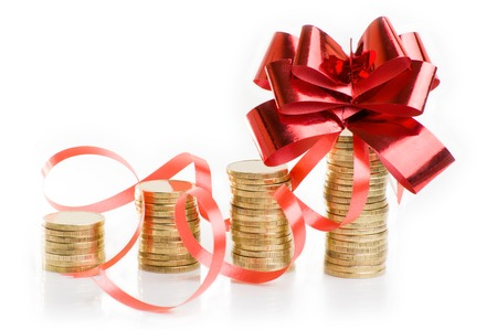 gold coins with a red gift bow. Concept of pecuniary profit. Stock Photo