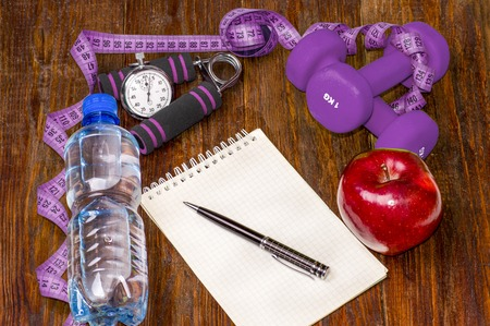 muscle fiber: Workout and fitness dieting copy space diary. Healthy lifestyle concept. Apple, dumbbell, water, expander hand, stopwatch and measuring tape on rustic wooden table.