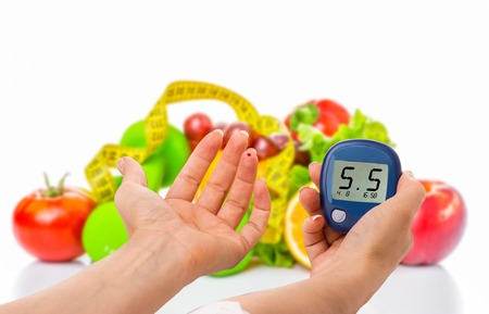 glucometer for glucose level and healthy organic food on a white background.