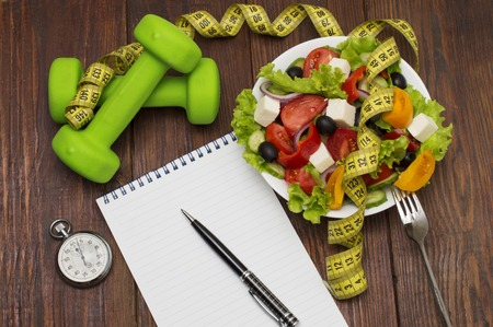 muscle fiber: Workout and fitness dieting copy space diary. Dumbbell, vegetable salad and measuring tape on rustic wooden table. Stock Photo