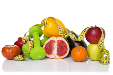muscle fiber: fitness equipment and healthy food isolated on white. green apple, pepper, kiwi, dumbbells and measuring tape