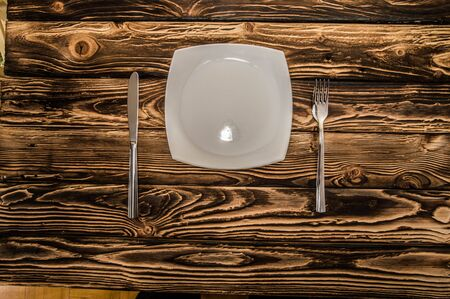 evenly folded cutlery on a wooden table Stock Photo
