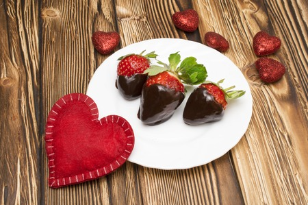 hot day: Fresh strawberries dipped in dark chocolate and heart on wooden background. Valentines Day