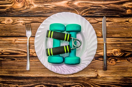 muscle fiber: Dumbbells, ball and expander on a plate as breakfast, concept of healthy lifestyle