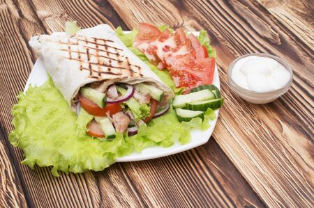 red onions: Shawarmas on lettuce isolated  a wooden background Stock Photo