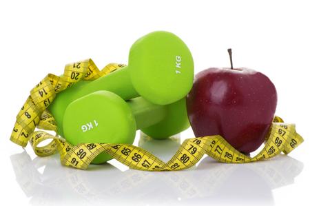 Two dumbbells, red apple, measuring tape.