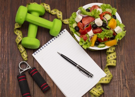 muscle fiber: Dumbbell, vegetable salad and measuring tape on rustic wooden table.