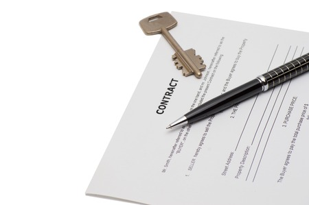 Keys of a new house on a signed contract of house sale with money in background. Concept of closed deal. Stock Photo
