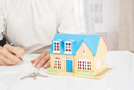autograph: woman with house model and pen signing contract document Stock Photo