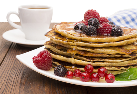 Delicious pancakes with berries and maple syrup