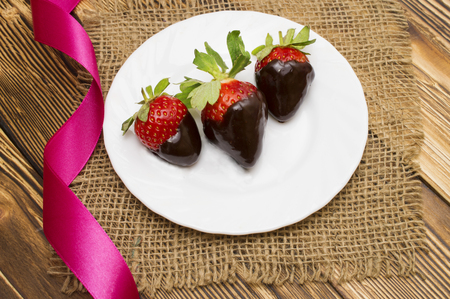 Fresh strawberries dipped in dark chocolate and heart on wooden background. Valentines Day