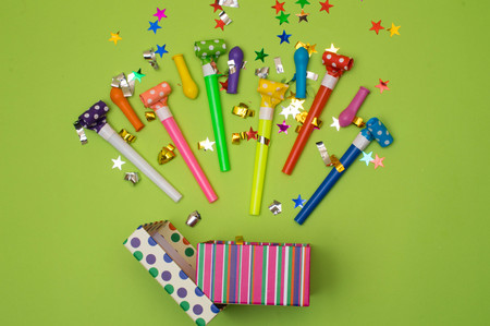 gift box with various party confetti, balloons, streamers, noisemakers and decoration on a green background. Colorful celebration background. Flat lay.