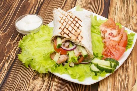 Shawarmas on lettuce isolated a wooden background