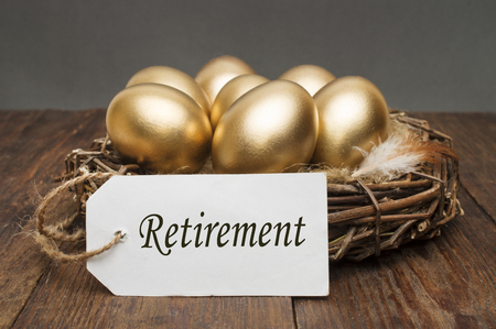 Nest with golden eggs with a tag and a word retirement on a wooden background. The concept of successful retirement Stock fotó